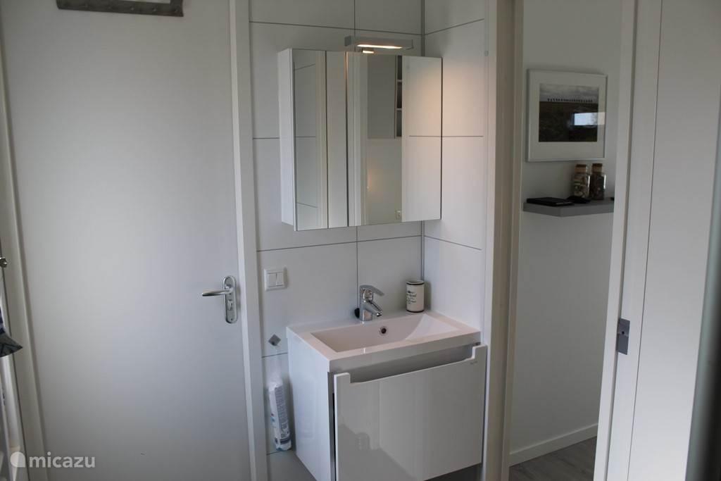 Boven de wastafel is een moderne toiletkast met stopcontact en verlichting. Onder de wastafel bevind zich een ruime schuiflade.