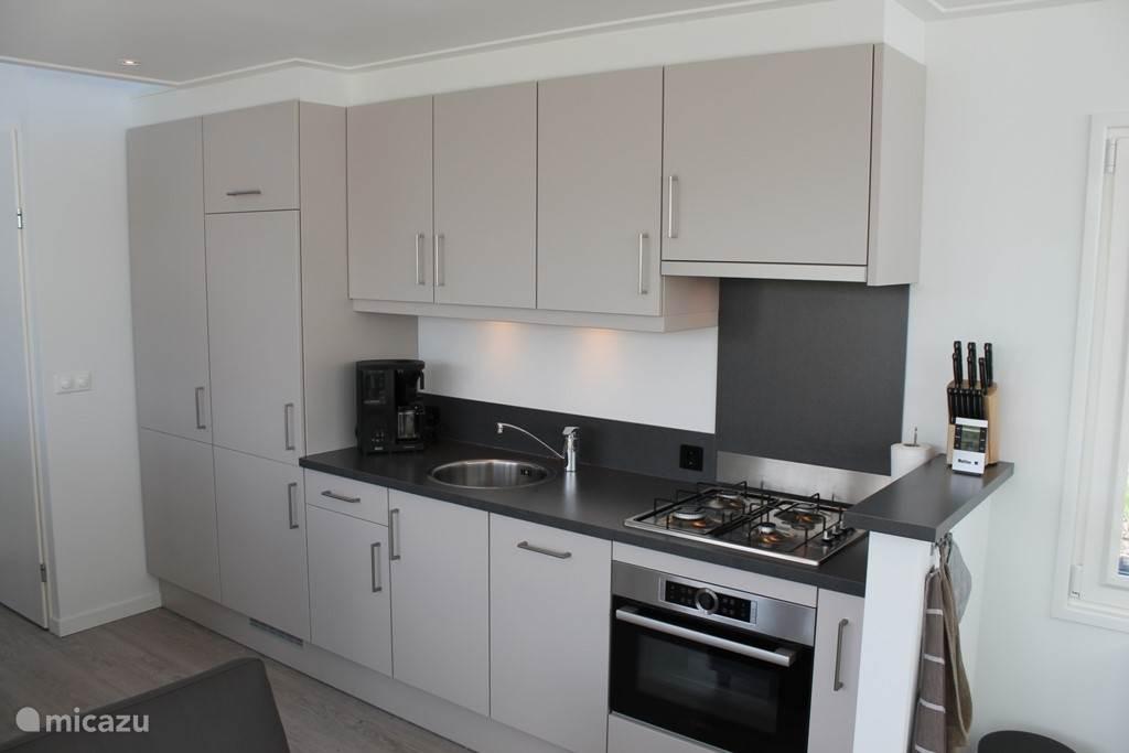 In de living is de keuken gerealiseerd voorzien van een koelkast met vriesvak, een magnetron-bakoven en een afwasmachine. Ook is het mogelijk de wasmachine te gebruiken.