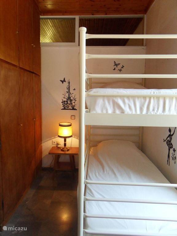 The bedroom with bunk beds and fitted wardrobe.