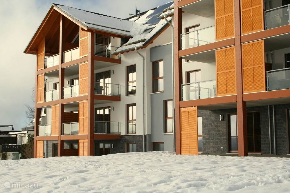 The apartment, seen from the ski slope. The balcony of the apartment is seen on the second floor, in the right row of the left part in the picture.