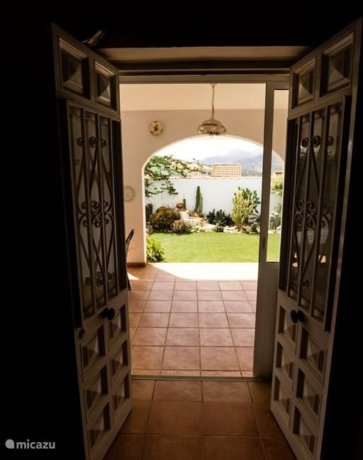 Doorkijk vanuit woonkamer naar veranda en tuin