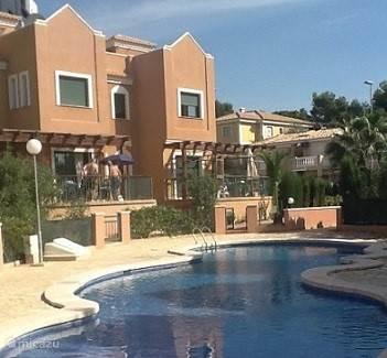 Aanzicht woning met ruim terras en zicht op het zwembad.