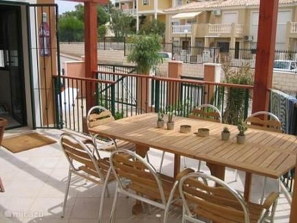 Ruim terras met tafel, stoelen en zitbanken.
