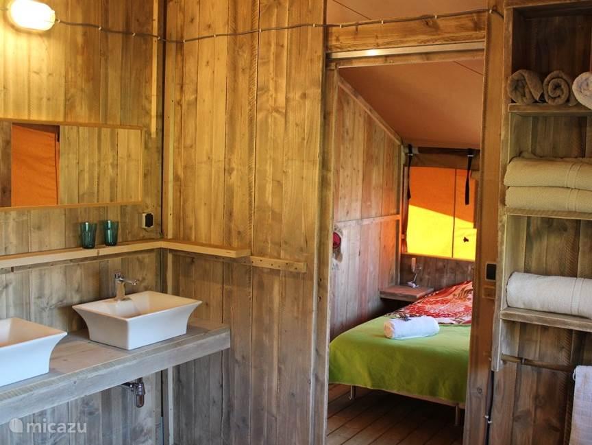 Badkamer met twee wastafels, douche en toilet. Schuifdeuren naar de twee slaapkamers.
