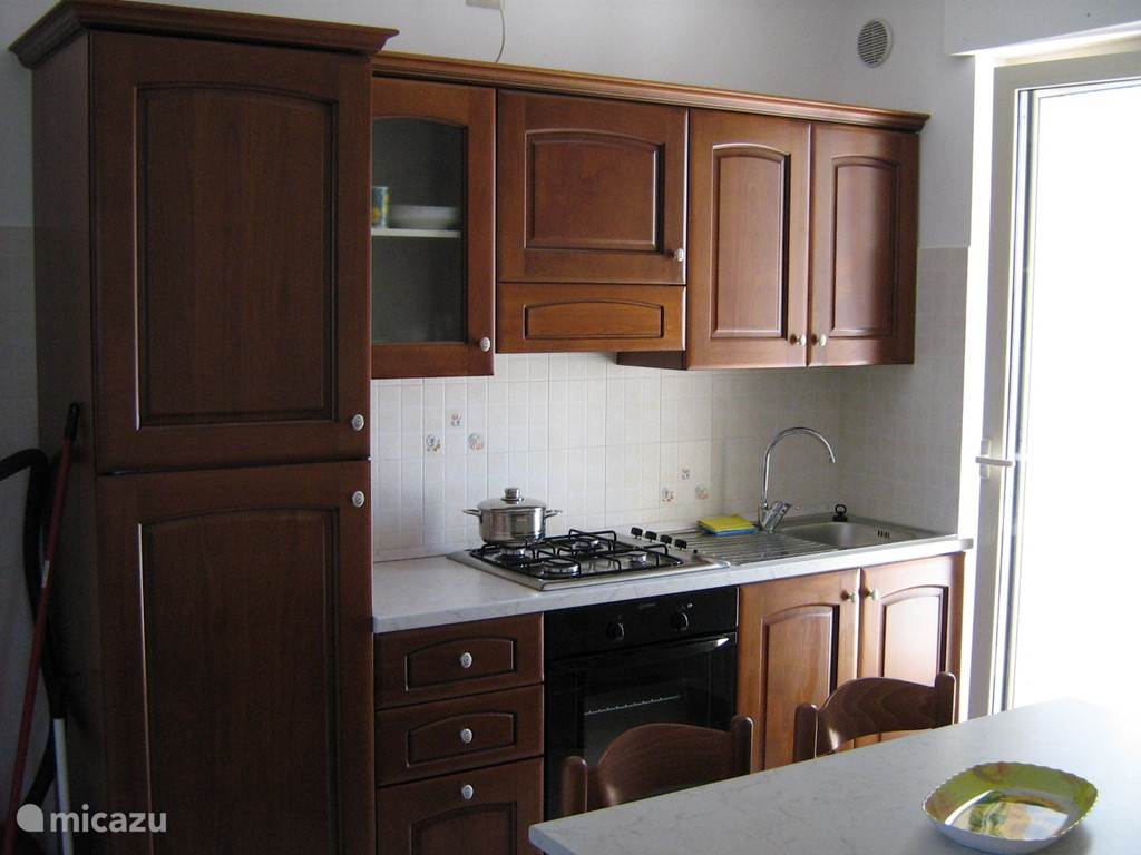Kitchen with stove and fridge freezer