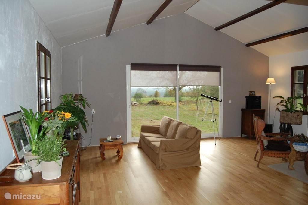 Ruime woon/leef ruimte met schuifpui die toegang geeft tot het zonnige terras met lounge set.