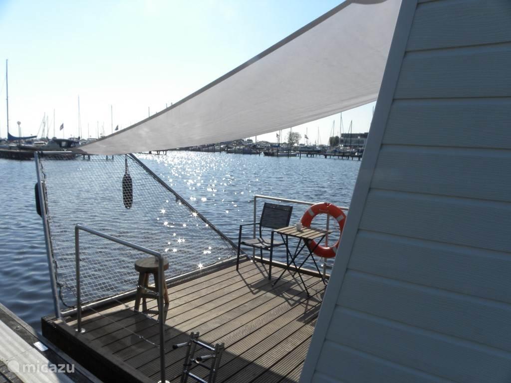 Heerlijk terras op het water met een zonneluifel