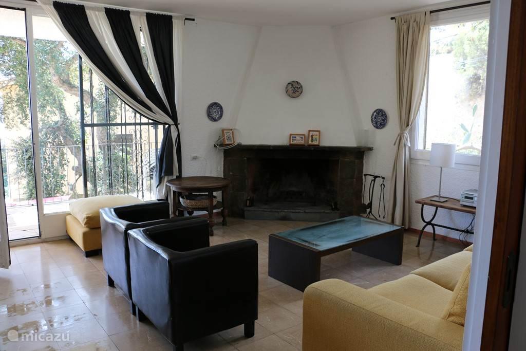 Woonkamer in het bovenhuis, met toegang tot het terras waarvandaan uitzicht op zee. En toegang tot het zijterras.
