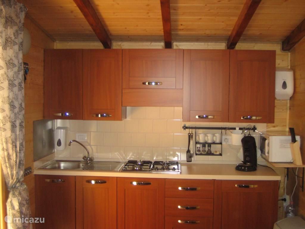 De keuken met 4 pits kookplaat, koelkast, senseo en magnetron.