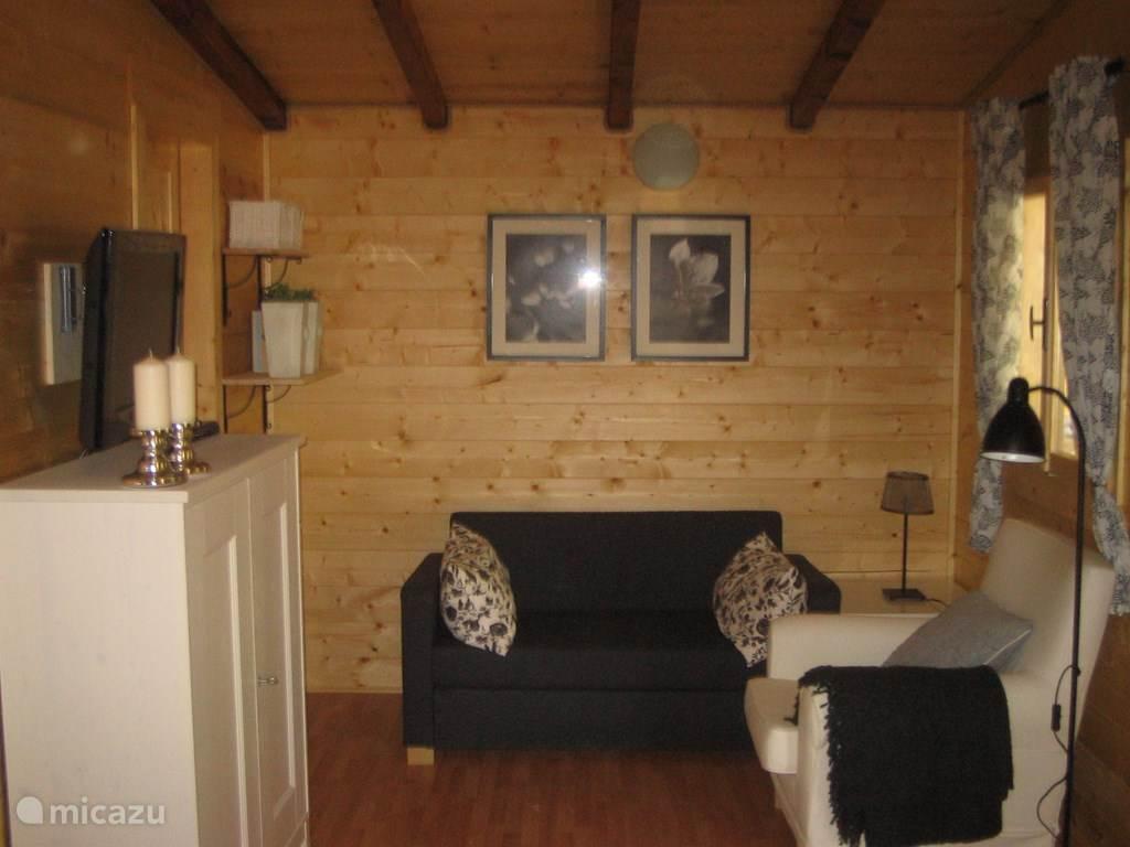 De woonkamer met slaapbank en sateliet TV met Nederlandse zenders