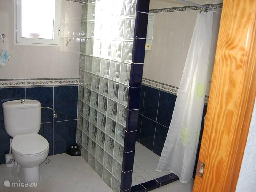 ruime badkamer met inloopdouche, wc en bidet.en wastafel.
