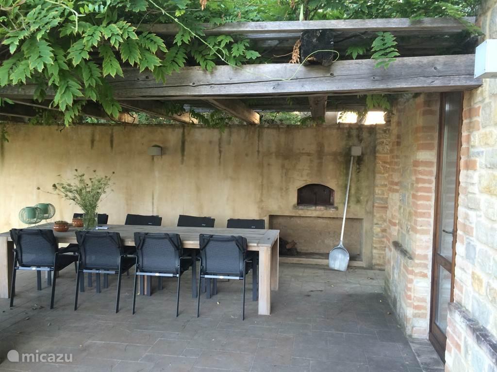 Het terras bij de keuken met lange eettafel en originele houtgestookte pizzaoven