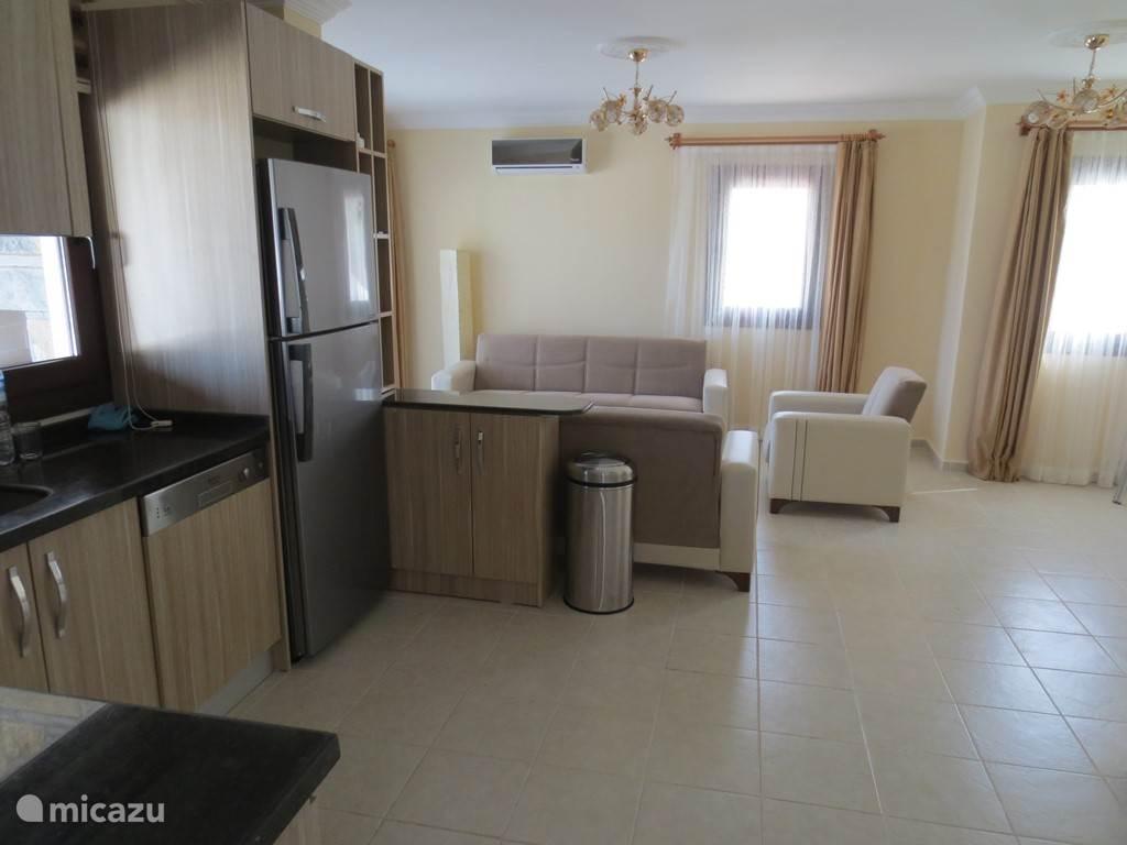 De woonkamer / keuken van het bovenste appartement