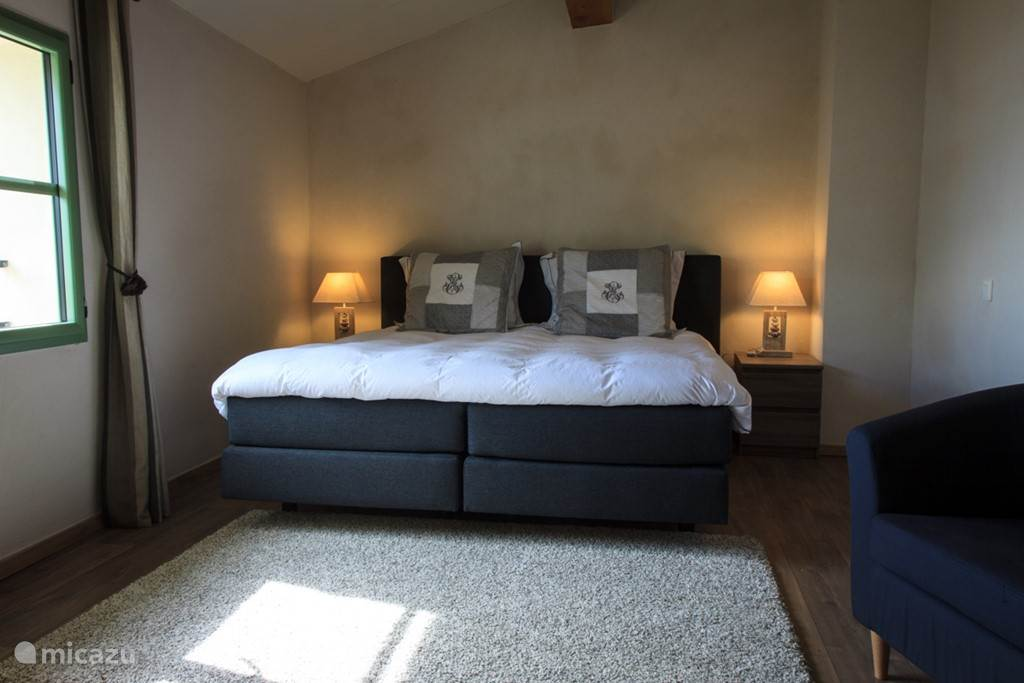 Bedroom with large double box spring bed.