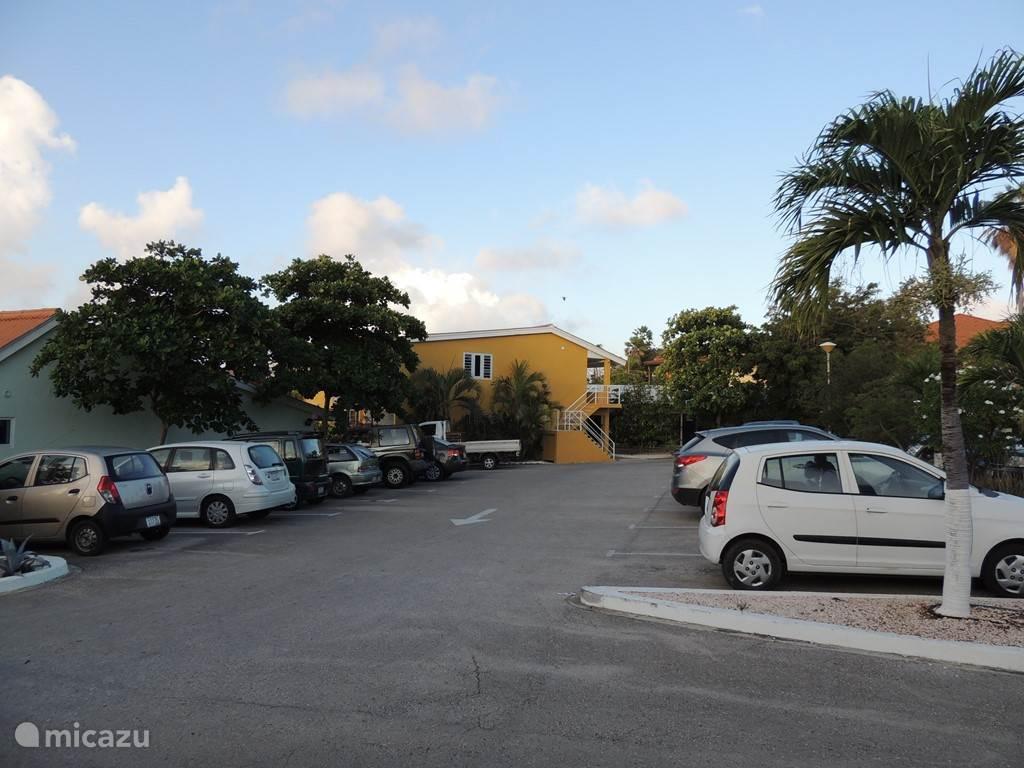 Ruime parkeerplaats tegenover het appartement. In de verte de zijmuur met de grote zijraam van het appartement. Het appartement ligt gunstig op de wind.