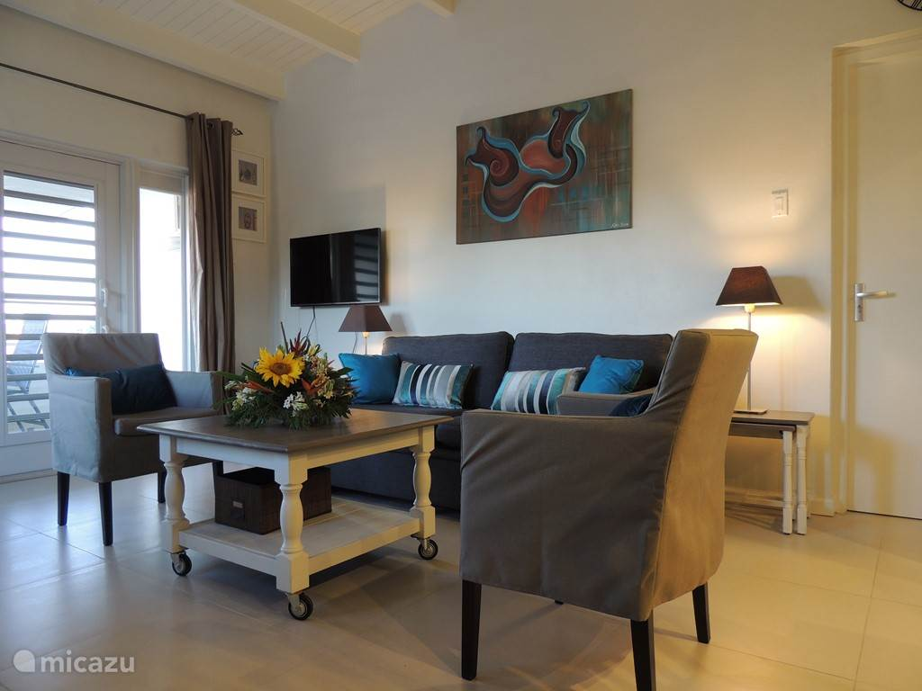 De smaakvol ingerichte woonkamer is licht en koel. Voorzien van vele gemakken.