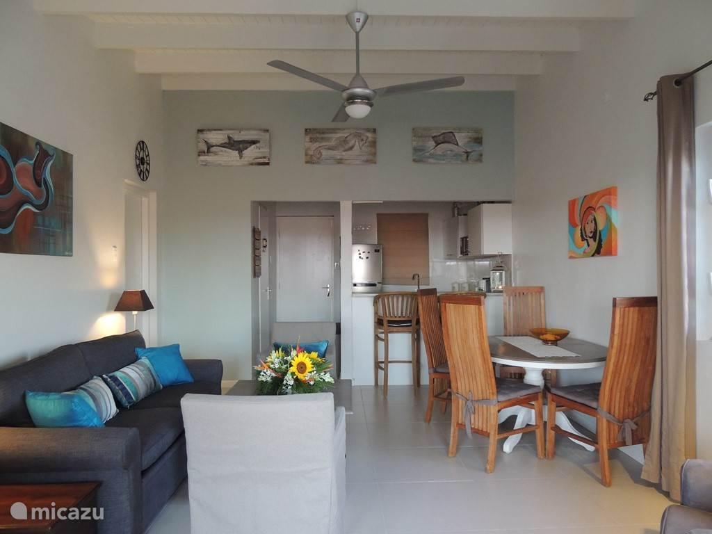 Overzicht van de woonkamer, open keuken, ingang, vanuit het balkon genomen.Met een groot zijraam (rechts).