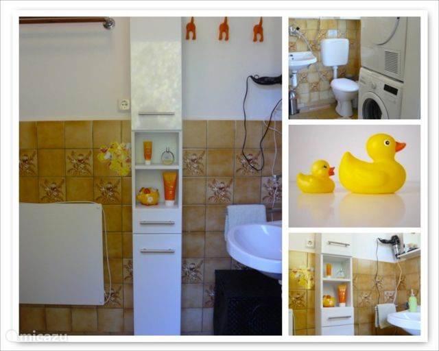 De authentieke DDR badkamer met föhn, wasmachine, wasdroger, wastafel en toilet.