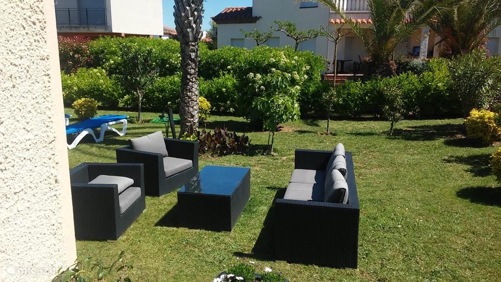 Tuin aan het zwembad met een loungehoek