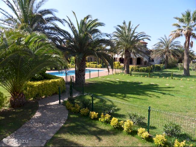 Tuin met gemeenschappelijk zwembad 12. mtr x 6.50 diep 1.10 mtr naar 2.00 mtr