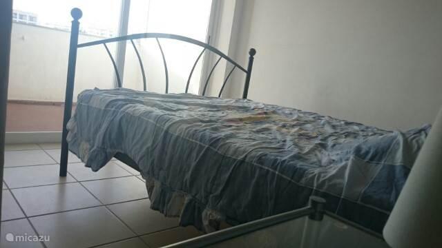 slaapruimte met schuifraam dat uigeeft op het balkon