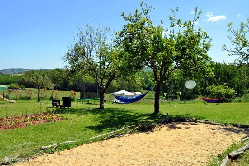 Het veld met jeu de boulesbaan, hangmat, stookplaats enzenz