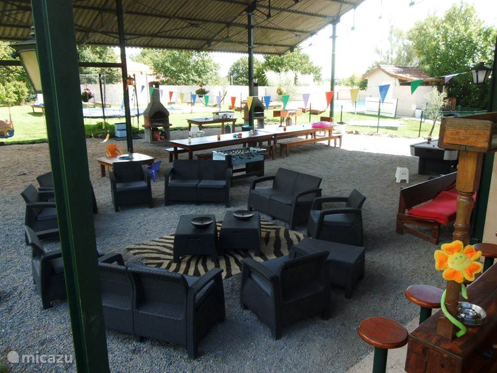 Covered area (16m x 16m) with lounge set and barbeque and plancha and bar.