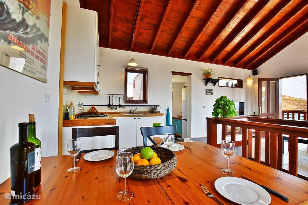 Eettafel met keuken en bijkeuken op de achtergrond