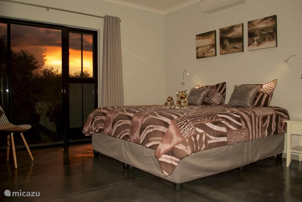 De tweede slaapkamer met kingsize bed en prachtig uitzicht op het zwembad en de bergen.
