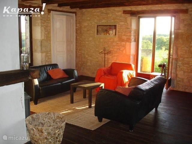 de woonkamer met 5 zitplaatsen zonnig en een houtkachel