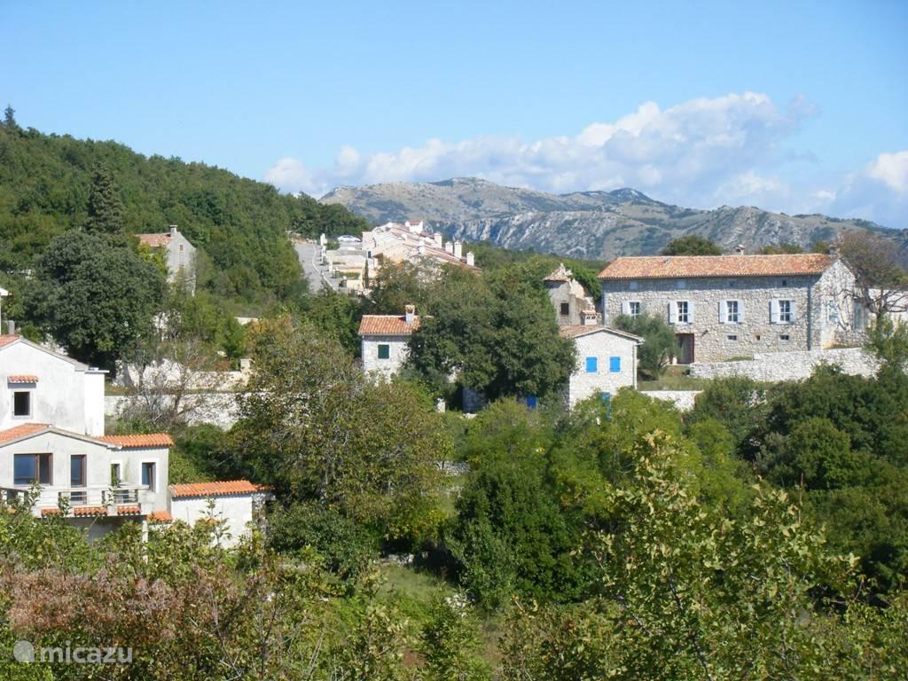 het dorp Mali Kosi, met het appartementencomplex en het Uckagebergte op de achtergrond.