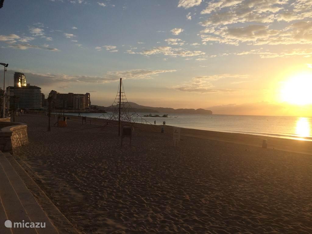 avondzicht op het strand voor de building met speel- en klimrek voor kinderen