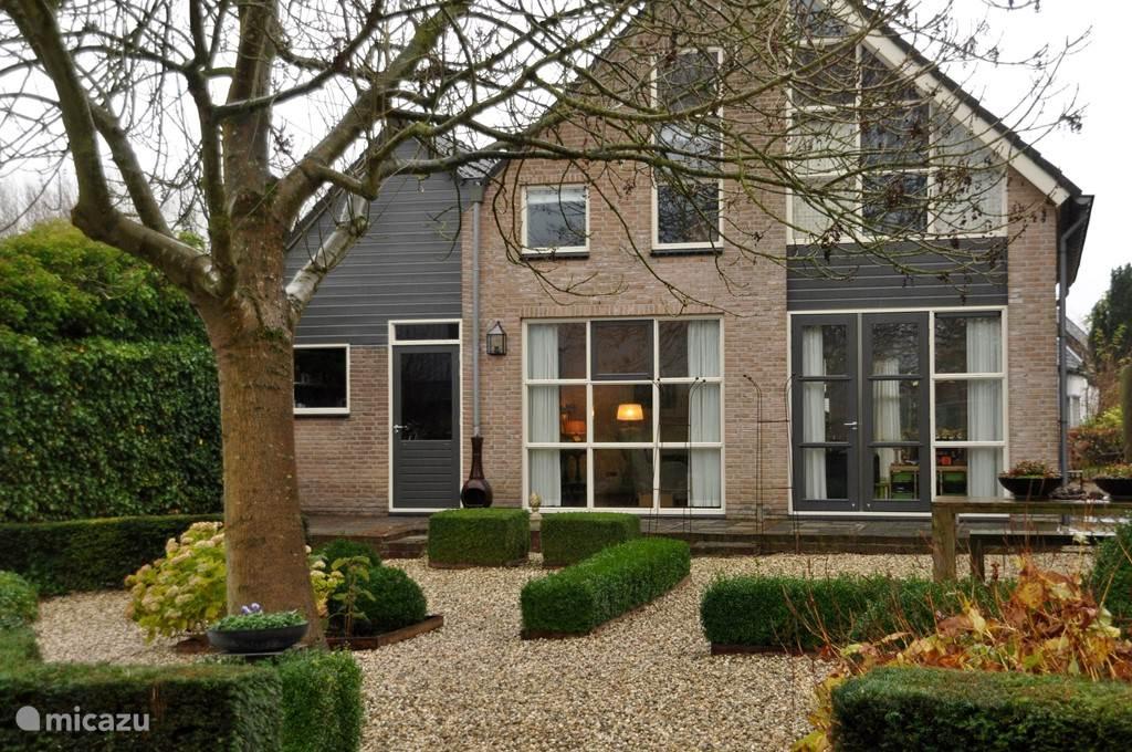 Achterkant huis met terras en tuin