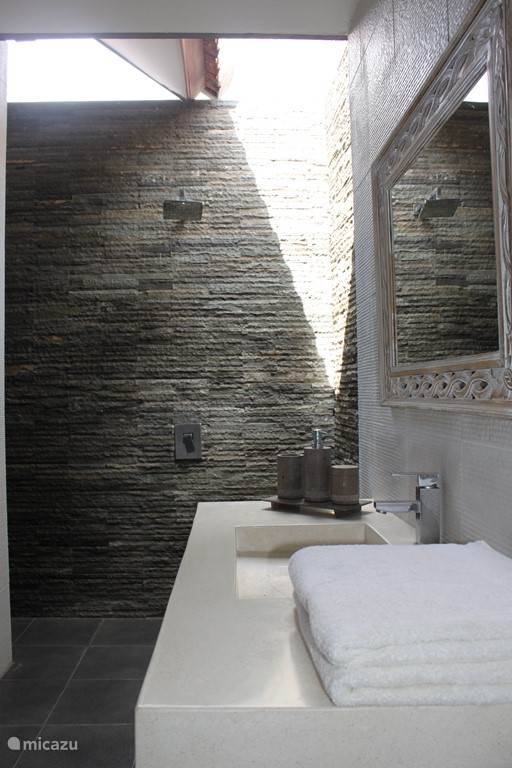 Spacious bathroom with outdoor shower. Towels and toilet kits are ready for you.
