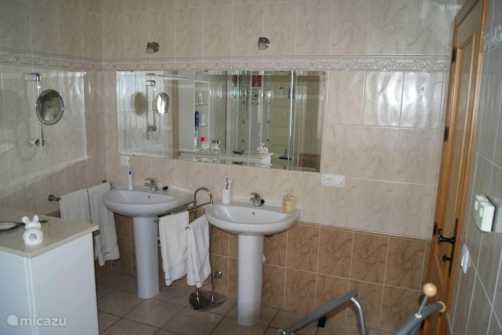 de badkamer van de grote slaapkamer met bad, douche, toilet en 2 wastafels
