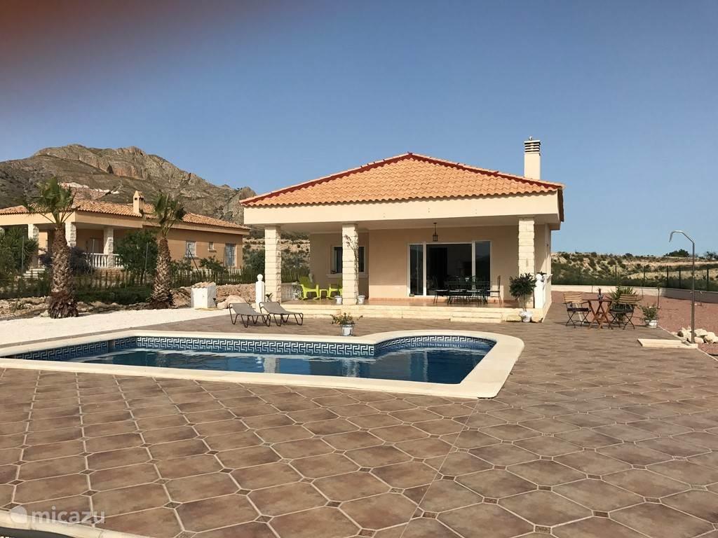 De villa staat naast 2 andere villa's en is omgeven door bergen en natuur