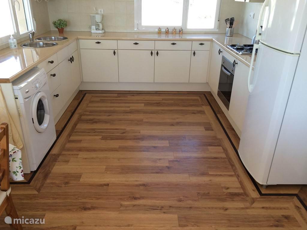 Ruimte lichte keuken met oven, wasmachine, grote koelkast met vriezer.