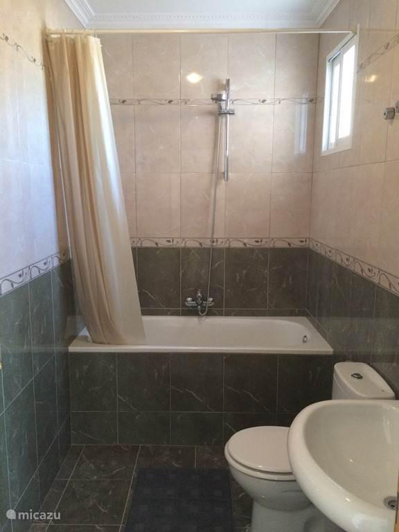 1 van 2 Badkamers  met ligbad, douche, toilet en wastafel.