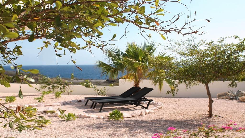 Even in de zon in een tropische tuin met zeezicht