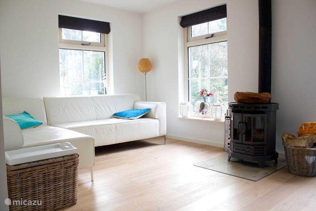 De zitkamer met lekker bank en houtkachel