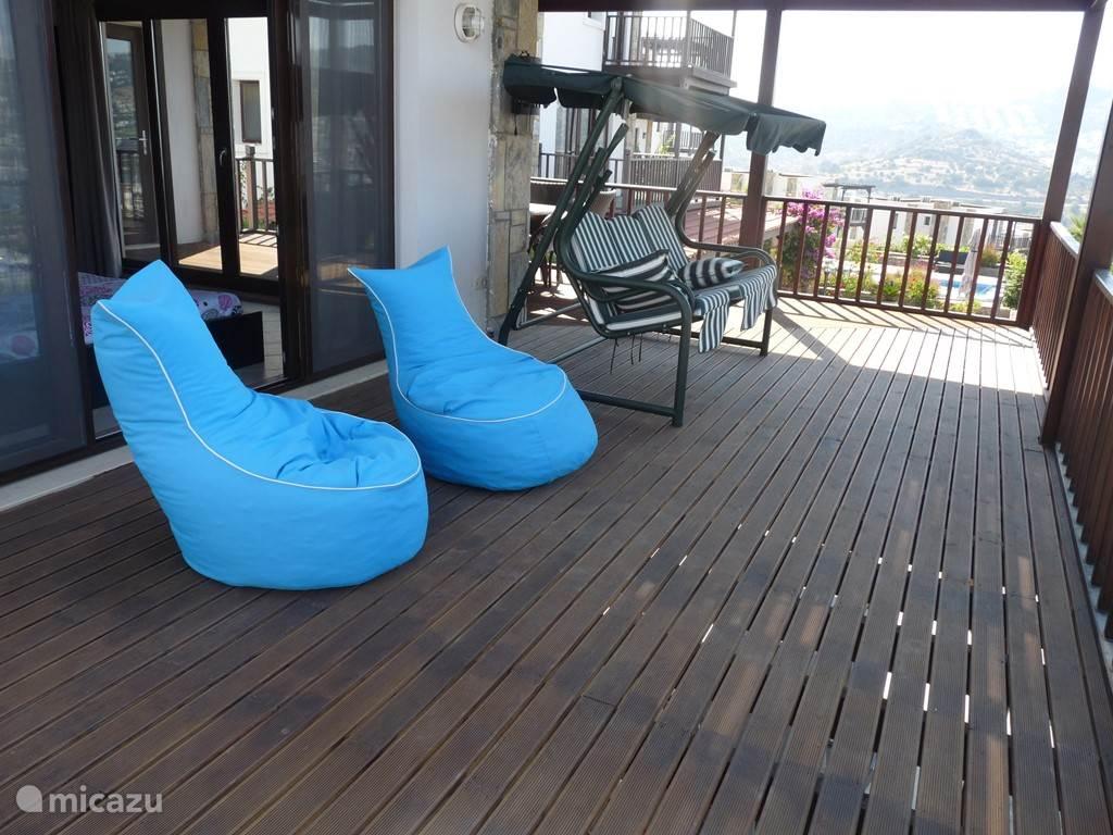 Terras verdieping 1 voorzien van zitzakken en schommelstoel  met uitzicht op de baai