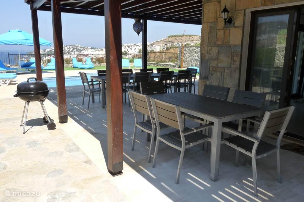 Eettafels onder terras voorzien van 16 stoelen en 3 tafels welke kunnen omgevormd worden tot 1 lange tafel met 14 stoelen