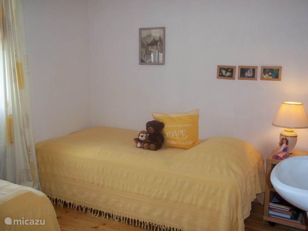 Kleine slaapkamer met 2 éénpersoons boxspring bedden.