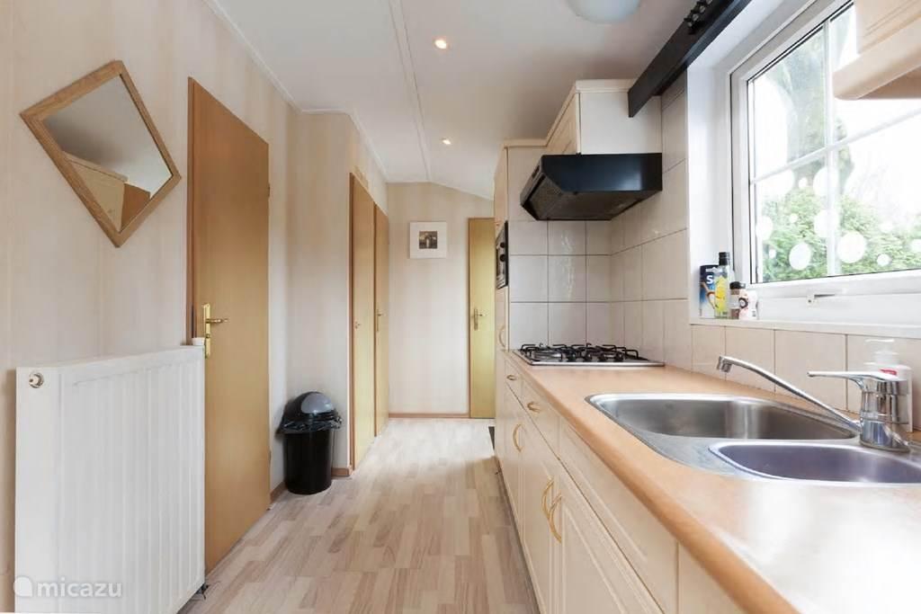 Keuken voorzien van koelkast met vriesvak, magnetron, filter koffiezetapparaat en waterkoker.