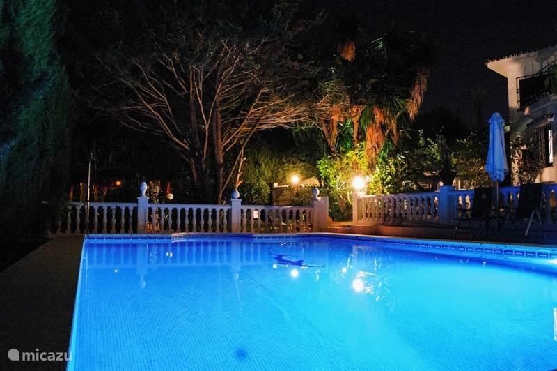 Zwembad verlicht bij nacht.