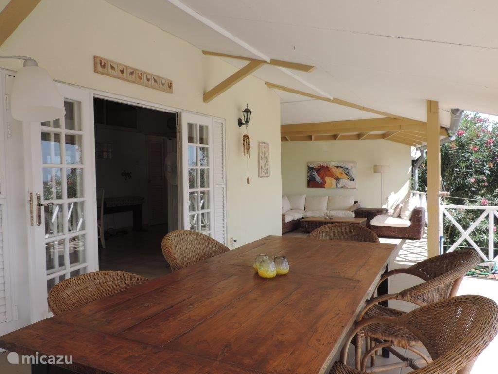 de porch met de eettafel en de zithoek