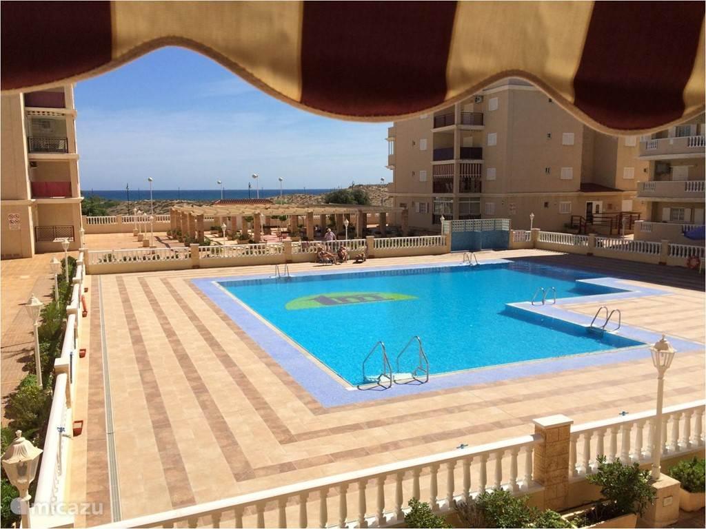 Zicht van op ons terras op het gemeenschappelijk zwembad en het strand en de zee