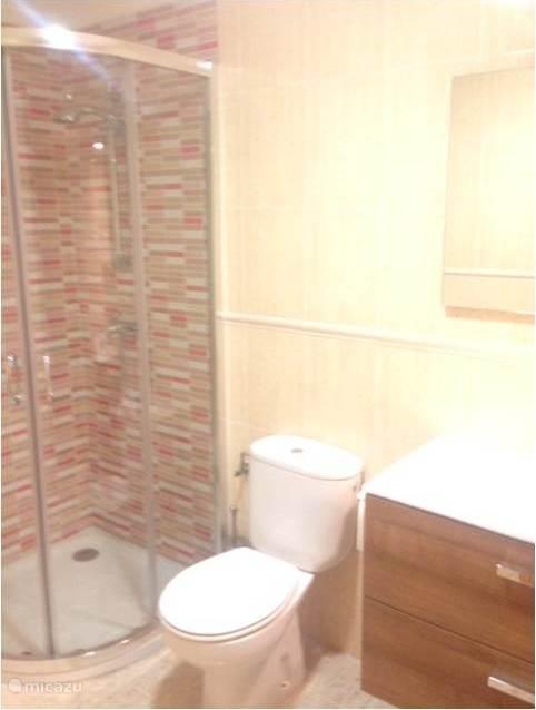 De mooie, moderne badkamer met douche, toilet en wastafel.