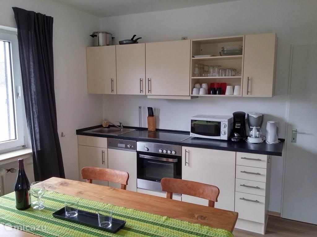 Luxe keuken met o.a. magnetron, oven, koffiezetapparaat en Senseo en een vaatwasser.
