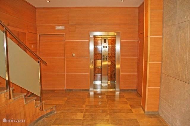 ingang van het appartementencomplex met zowel een lift als een trap